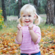 In the autumn forest little blonde girl enthusiastically shouts — Stock Photo