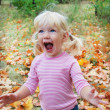Stock Photo: In autumn forest little blonde girl enthusiastically shouts