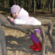Beautiful little girl playing in the roots of a tree. — Stock Photo