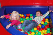 Boy to a girl playing in the pool with colorful balls. — Stock Photo