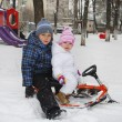 Stock Photo: The boy with a little girl sitting on a sled.
