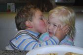 Café little boy kisses girl she was embarrassed. — Stock Photo