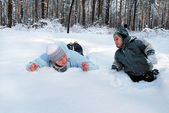 Winter mother with her son indulge lie on the snow in the forest — Stock Photo