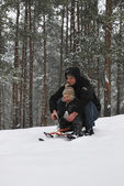 Father and son sledding with mountains in the winter snowy fores — Stock Photo
