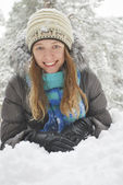 Wintet, lies the beautiful long-haired girl in the snow. — Stock Photo