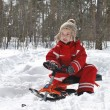 In winter, in forest boy is sitting on sled and smiling. — Stock Photo #38591097