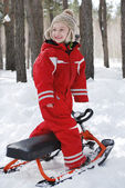 Winter in the woods stands a boy on snow scooter and smiling. — Stock Photo