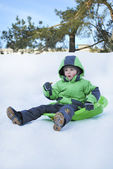 Boy riding the hills on sleds — Stock Photo