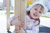 A little girl playing on the playground and laughs. — Stockfoto