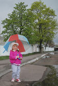 In the spring of a little girl standing under an umbrella on th — Stock Photo