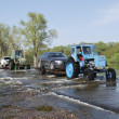 Floods, it flooded road tractor carries cars. — Stock Photo #39132655