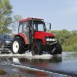Floods, it flooded road tractor carries cars. — Stock Photo #39211981