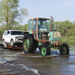 Floods, it flooded road tractor carries cars. — Stock Photo #39211989