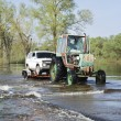 Stockfoto: Floods, it flooded road tractor carries cars.