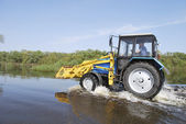 Tractor across the river which came out of its banks and flooded — Stock Photo