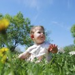 Little girls sitting in a field dandelions. — Stock Photo