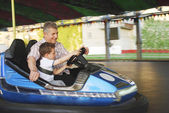 In the park on the rides grandfather with his grandson go by car — Stock Photo