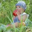 Girl sits in a birchwood on the grass and eats an apple — Stock Photo
