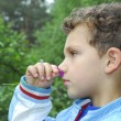 Summer in the woods a curly boy smelling pink flower. — Stock Photo #39529599