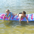 Summer on the river boy and girl floating on an air mattress. — Stock Photo