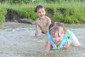In summer, the river indulge boy and girl, they are catching up — Stock Photo