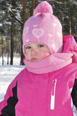 Little girl in a pine forest in winter. — Foto de Stock