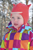 Little girl in a pine forest in winter. — Stock Photo
