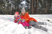 L little girl with her mother lying on the snow in the pine fore — Stock Photo