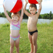 Stock Photo: Lake little boy and girl playing with inflatable ball