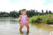 A little girl swims in the river. — Stock Photo