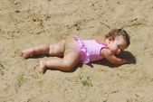 Summer little funny, dirty girl sunning at the lake in the sand — Stock Photo