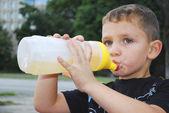 Street boy drinks water from a bottle. — Stock Photo