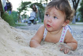 Dirty little girl lying in the sand near the playground. — Stock Photo