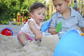 Brother and sister playing in the sand on the playground. — 图库照片
