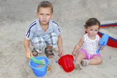 Brother and sister playing in the sand on the playground. — Stock Photo