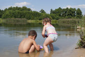 Young children playing on the beach near the lake. — Stock Photo