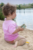 On the beach near the lake in the sand little girl playing with — Stock Photo