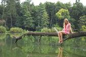 Meisje, zittend op de oever van het meer op de boom. — Stockfoto