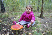 Girl sitting in a forest near the fly agaric — Stockfoto