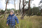 In the forest, in the tall grass is a littlel boy. — Stock Photo