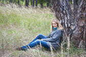 Girl sitting in tall grass near a pine tree. — Stock Photo
