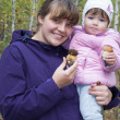 Stock Photo: Mother and little daughter in forest are holding mushrooms.