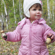 Stock Photo: Girl in birch forest holding mushroom.