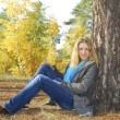 Girl sitting in autumn forest. near a pine tree. — Stock Photo