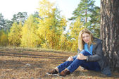 Jeune fille assise dans la forêt d'automne. près d'un pin. — Photo