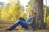 Girl sitting in autumn forest. near a pine tree. — Stock fotografie