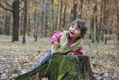 in the forest little girl playing near the stump. — Stock Photo