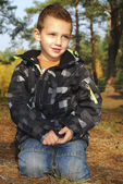 Boy sitting in autumn pine forest on earth. — Photo