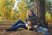 Mother and son in autumn forest. — Stock Photo