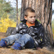 Forest little boy sits near a pine. — Stock Photo